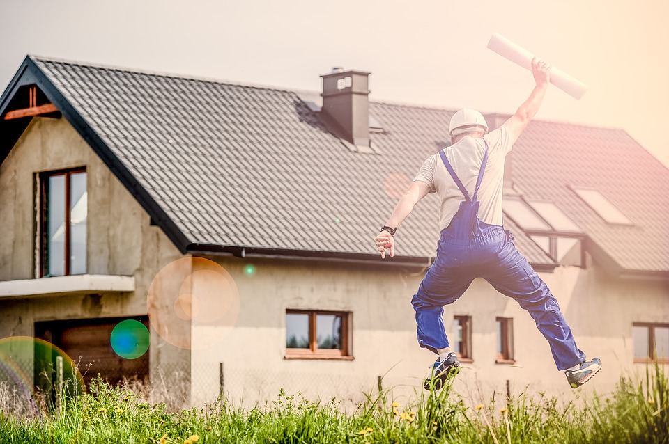 contractor jumping in front of house
