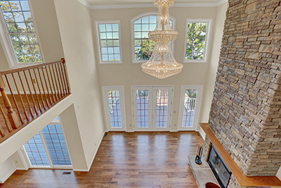 Two Story French Doors, Chandelier, and Fireplace View From the Second Floor